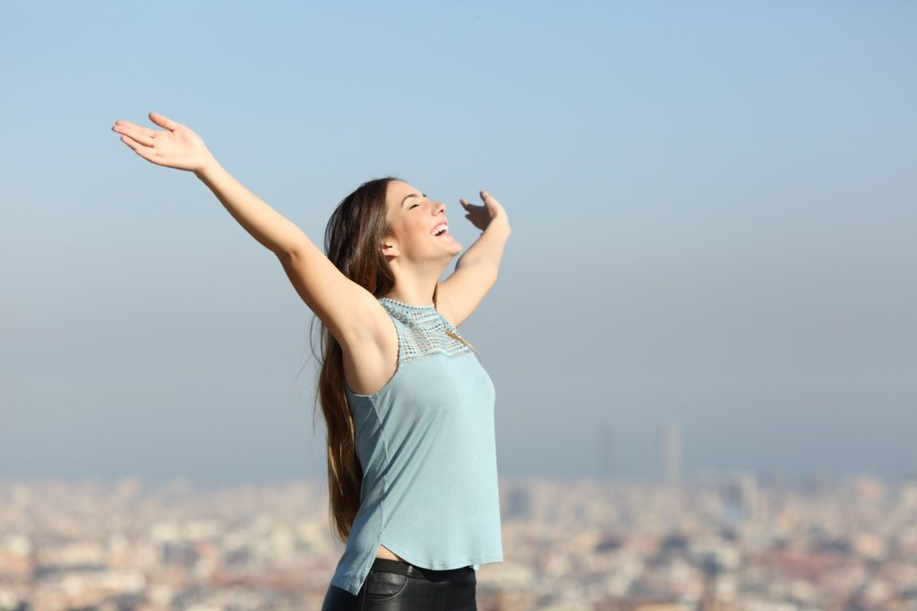Excited woman raising arms celebrating vacation with a city in the background
